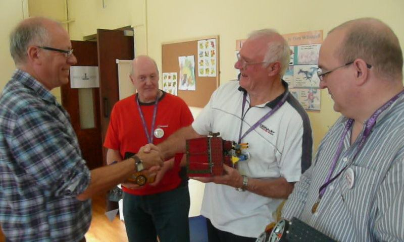 Chris Warrell presents the gold medal to Alan Wenbourne (centre) for the Push-of-War competition at our show on 13th October 2012. Chris Fry (in red) won silver and Ralph Laughton won bronze