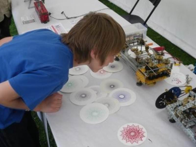 A boy examines the intricate workings of Peter Clay's Meccanograph