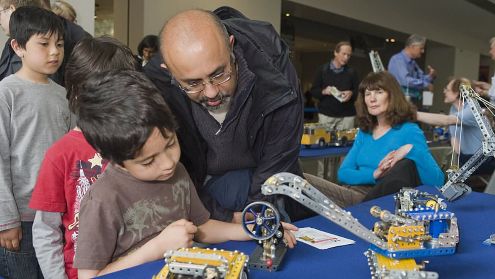 A family are fascinated by Chris Fry's models (Photo: NMM)