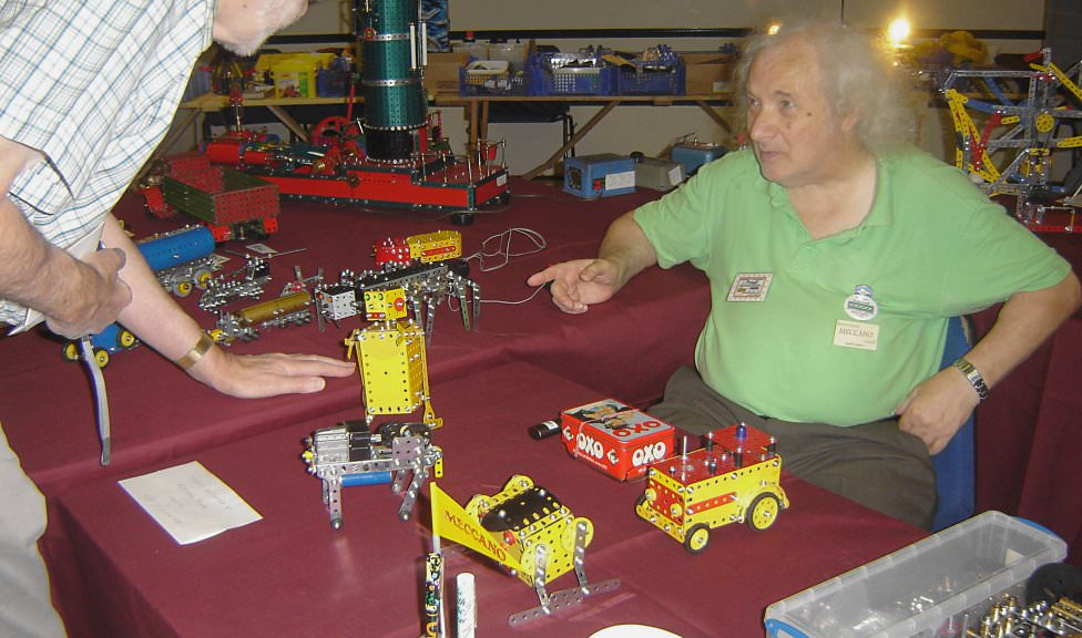 Geoff Carter at the International Meccano Model Show 2008, with a typical collection of small models (Photo: NZMeccano)
